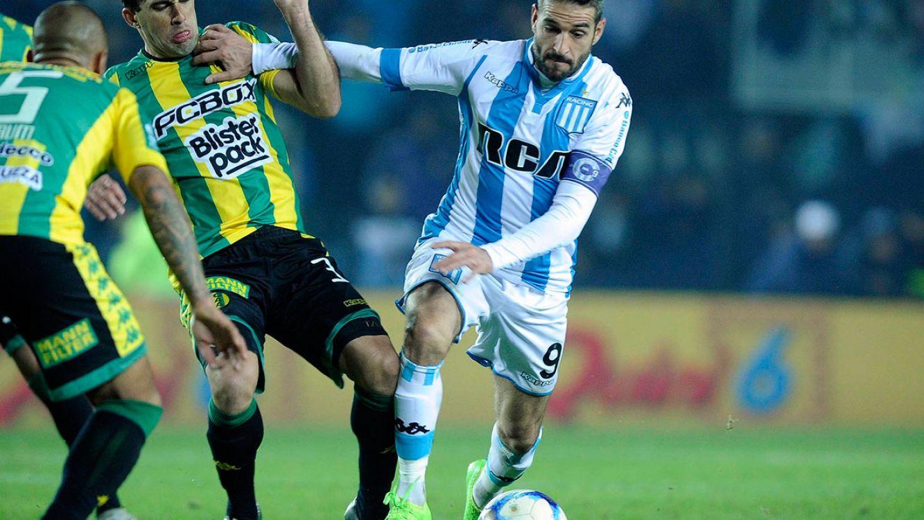 Lisandro Lopez de Racing Club disputando la pelota con los defensores de Aldosivi