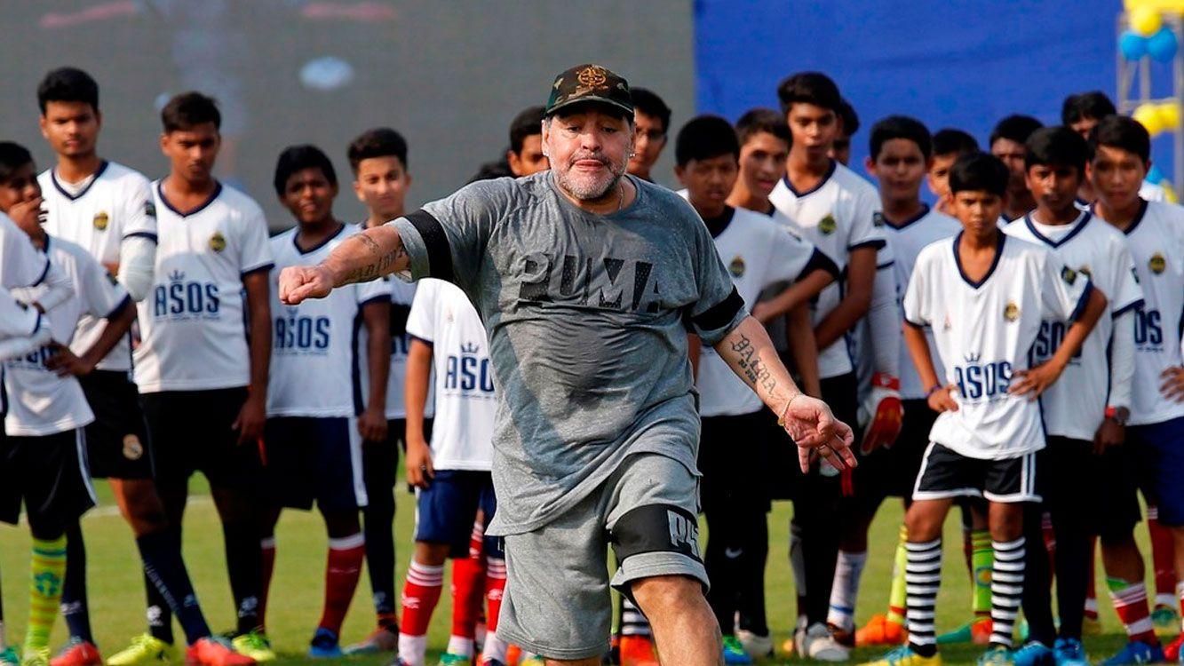 Diego Maradona patea la pelota ante la atenta mirada de los atentos estudiantes que asistieron a su clínica de fútbol.