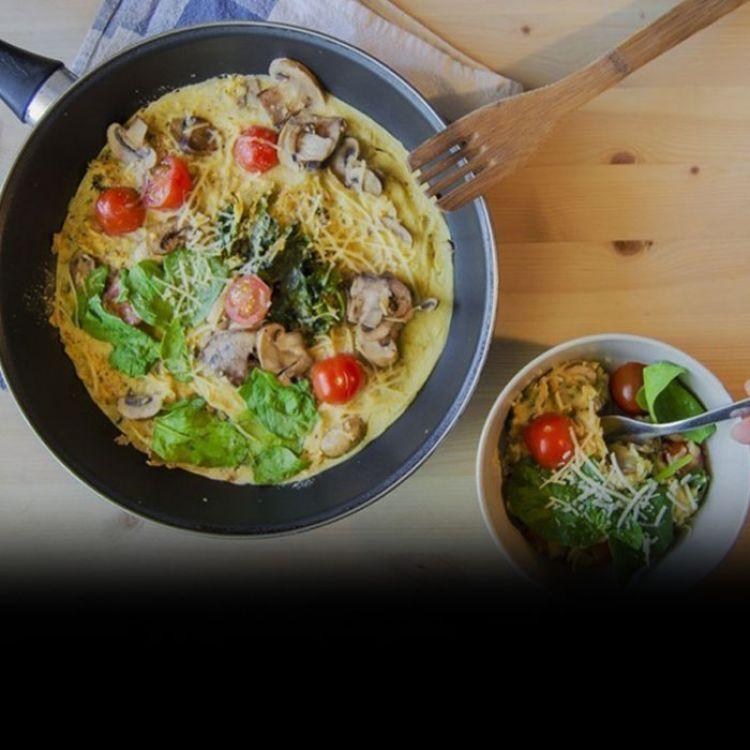 Una tortilla u omelette de harina de garbanzo. En este caso está rellena de espinaca y champiñones.